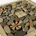 inserto 30x30 con cornice formata da listelli , tozzetti centrali, fiori spaccati a martello tutto in marmo e riempimento con sassi di fiume