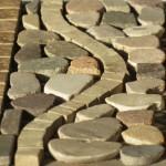 mosaico onda 15x30 con cornice con tozzetti in porcellanato 2,3x2,3 onda in porcellanato spaccata a martello e riempimento con sassi di fiume